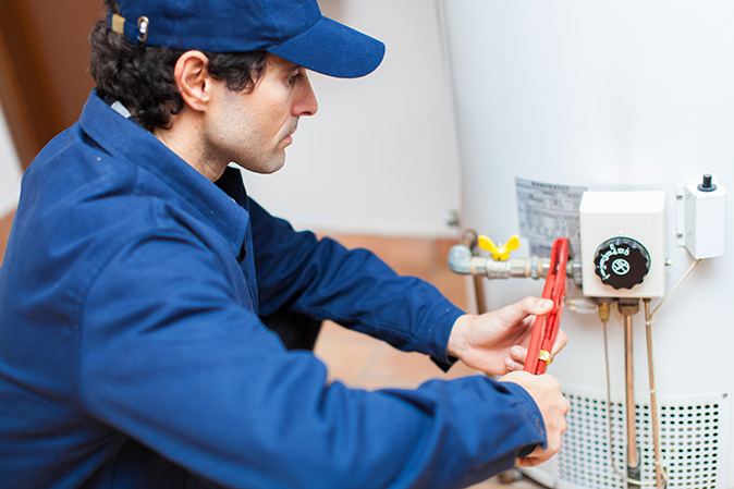 Plumber servicing hot water system