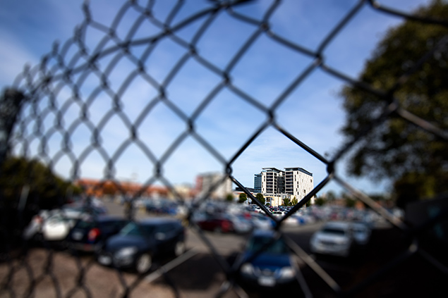 Apartment building seen through mesh fencing
