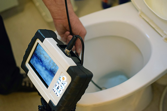 Plumber checking blocked toilet with endoscope