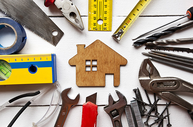 Wooden house cut-out surrounded by tools