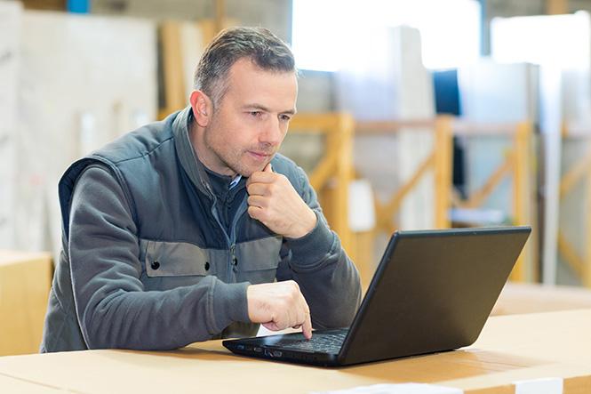 Worker on laptop in workshop