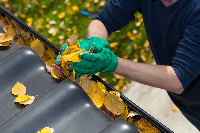 Man cleaning leaves from a gutter
