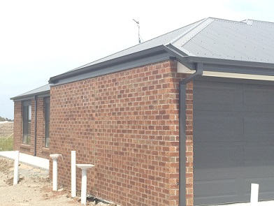 Example of a typical domestic garage wall on the title boundary with a non-compliant fire-resisting wall. Excessive metal flashing between the top of the brick wall and the underside of the gutter can be seen.